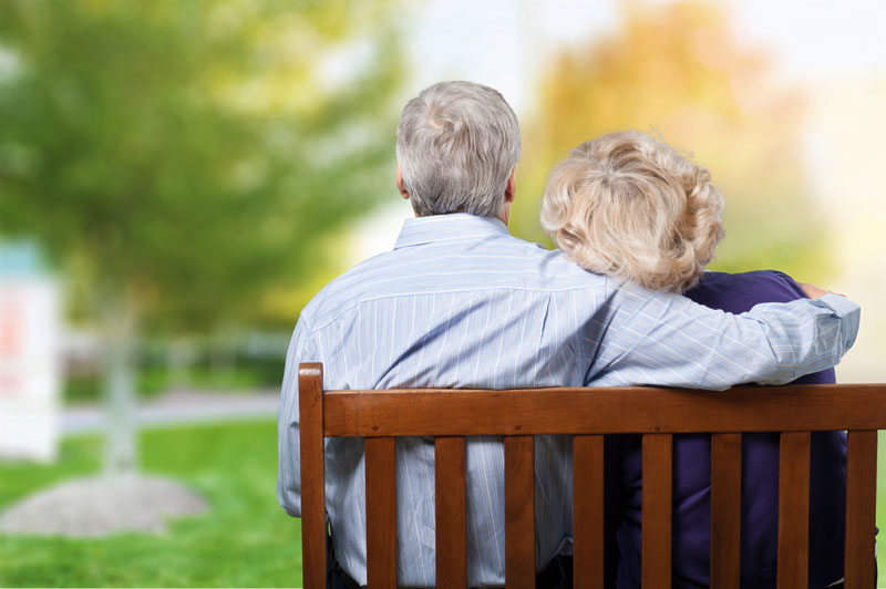 an elderly man and woman on a bench